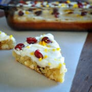closeup photo of a cranberry bliss bar with the baking dish in the background