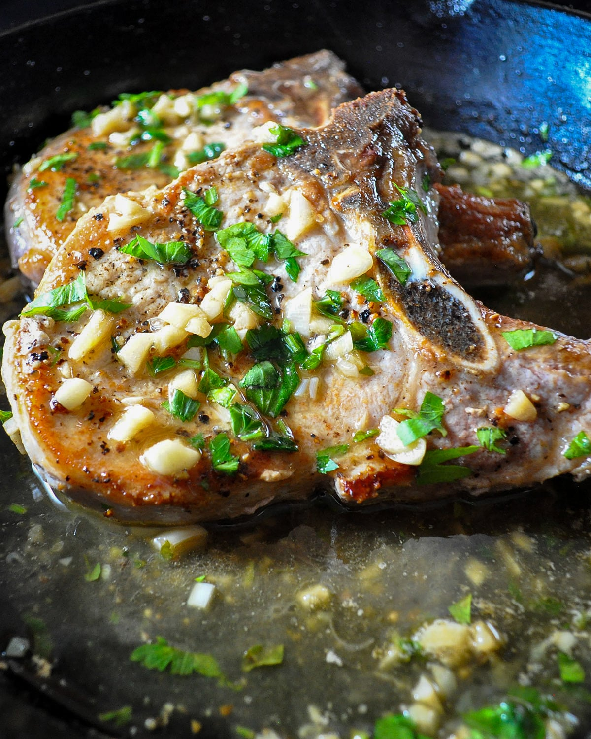 browned pork chops with garlic wine sauce in a skillet