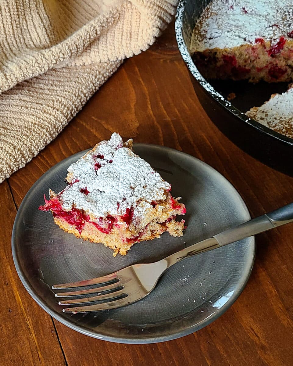 a half eaten piece of cranberry cake on a plate