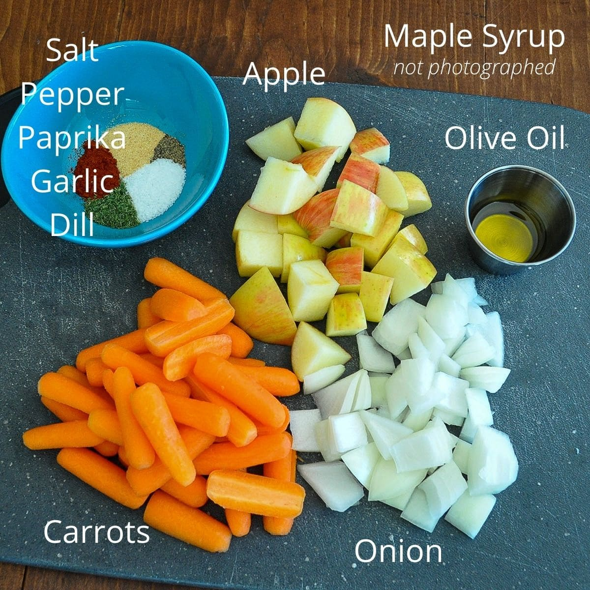 carrots, apples and onion on a cutting board next to a bowl of spices