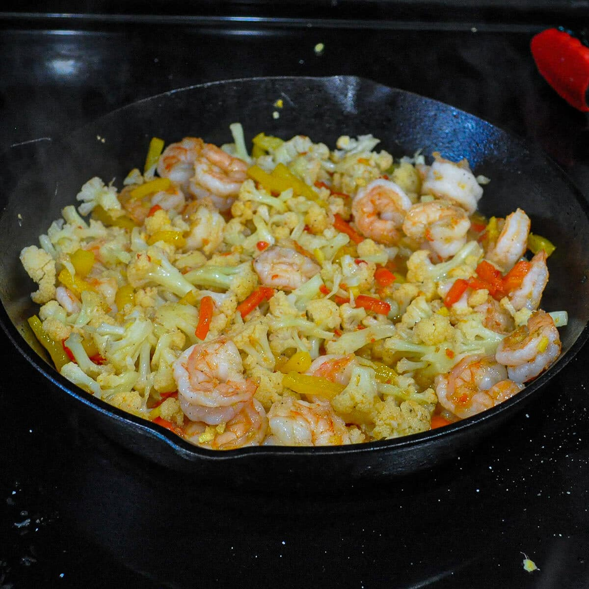 shrimp with cauliflower and peppers cooking in a skillet