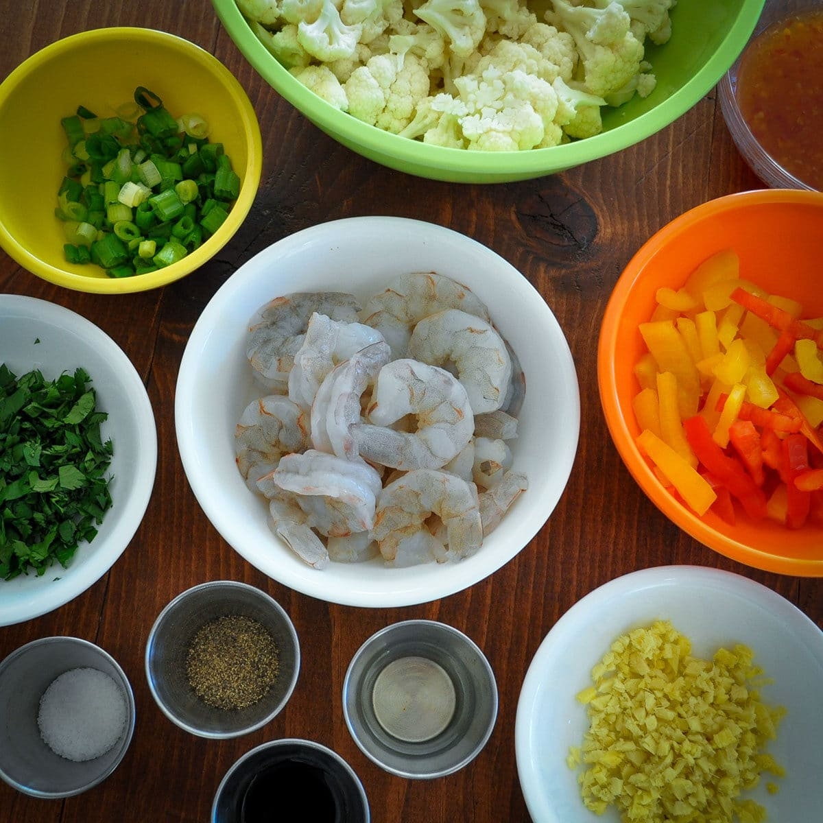 Bowls with ingredients for shrimp and cauliflower stir fry