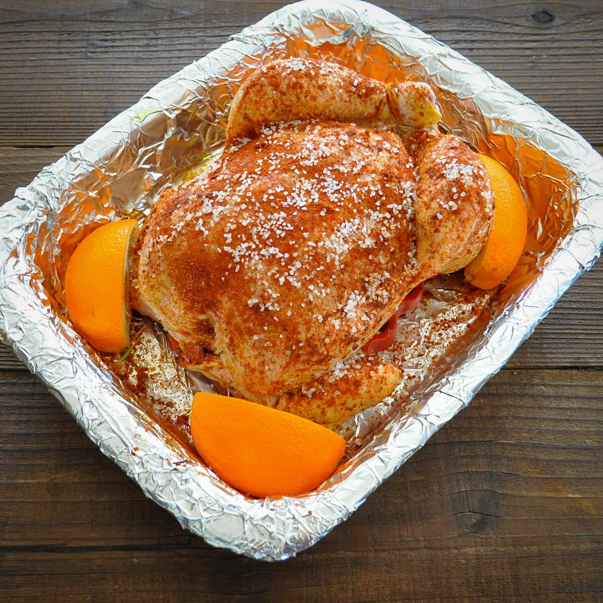 raw chicken in a baking dish with oranges
