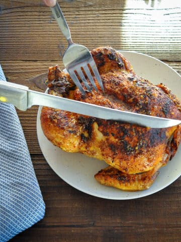 whole roasted chicken being sliced with a knife