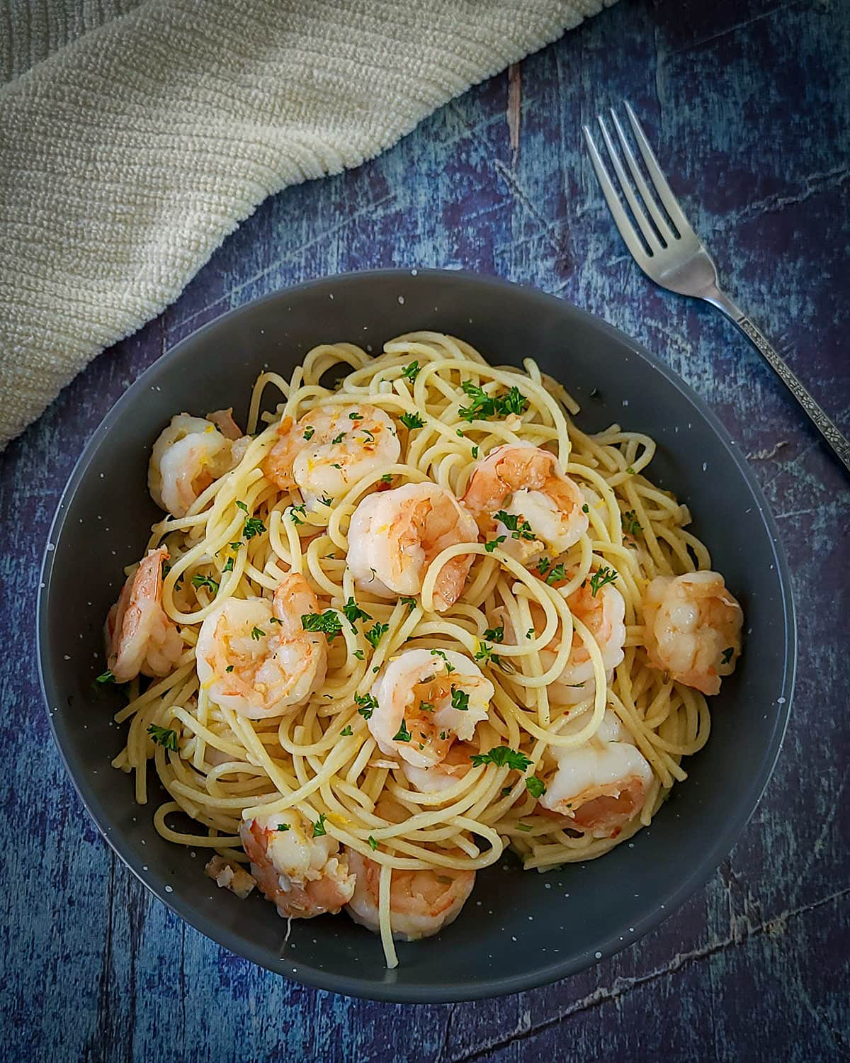 a bowl of spaghetti topped with shrimp