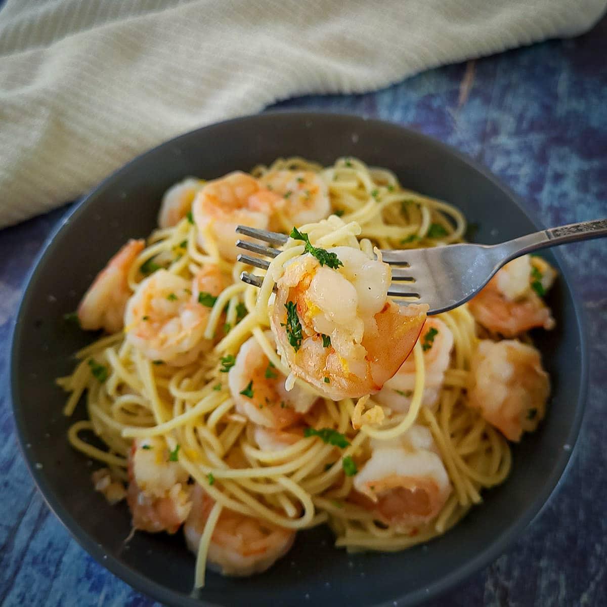 spaghetti with lemon shrimp in a gray bowl