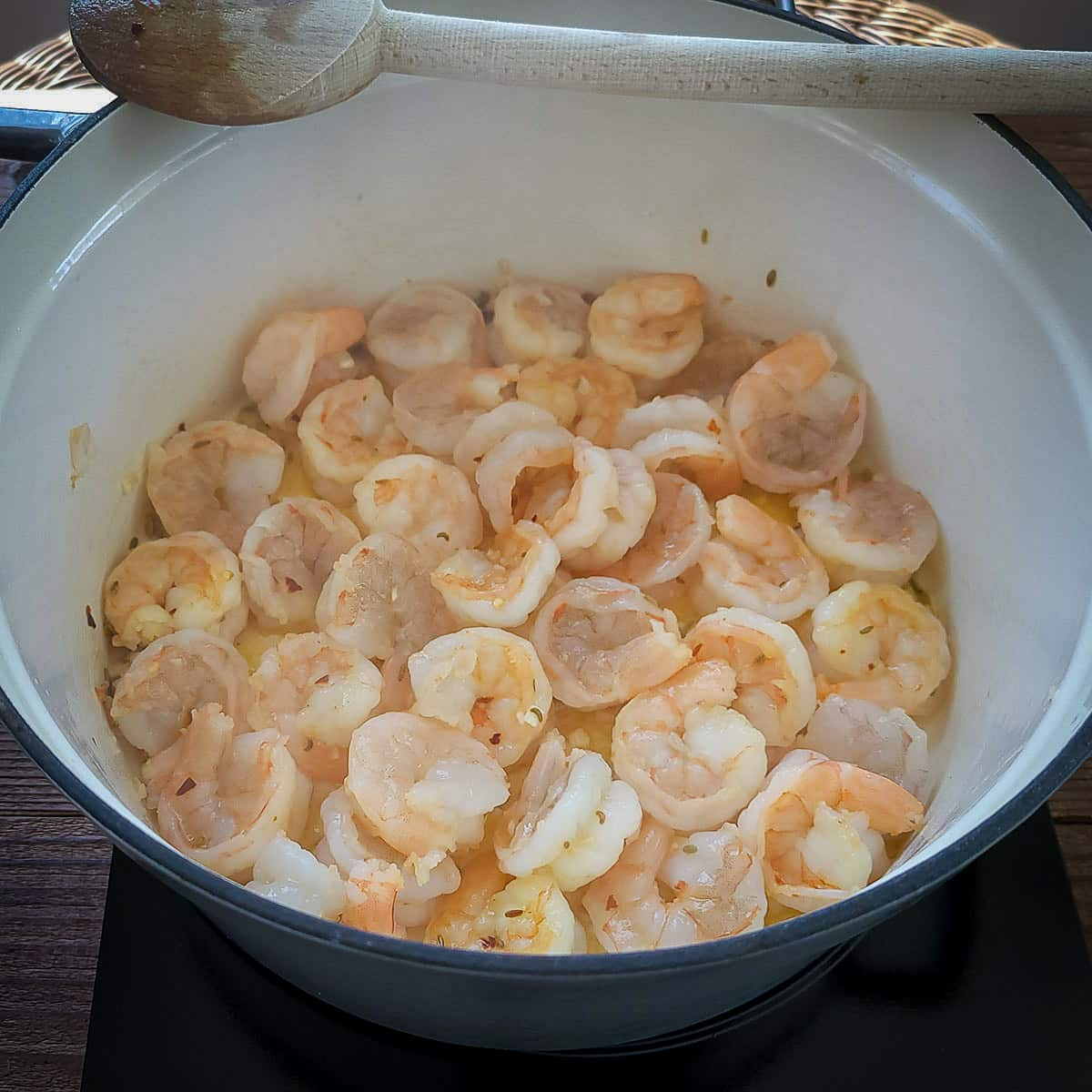 a large pot cooking shrimp with garlic in olive oil and butter