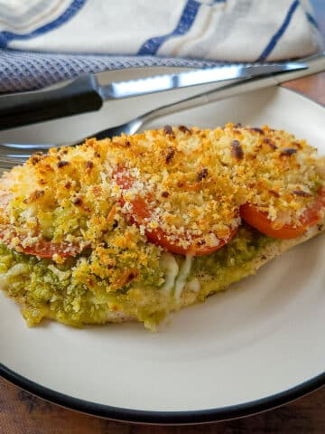 baked chicken breast with pesto, tomato and cheese on a plate