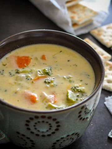 broccoli cheese soup in a bowl with crackers