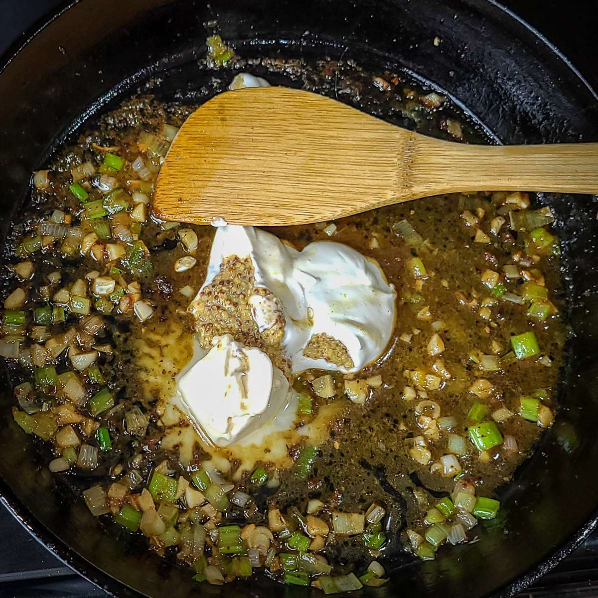 green onions, garlic, sour cream, dijon mustard and butter in a skillet