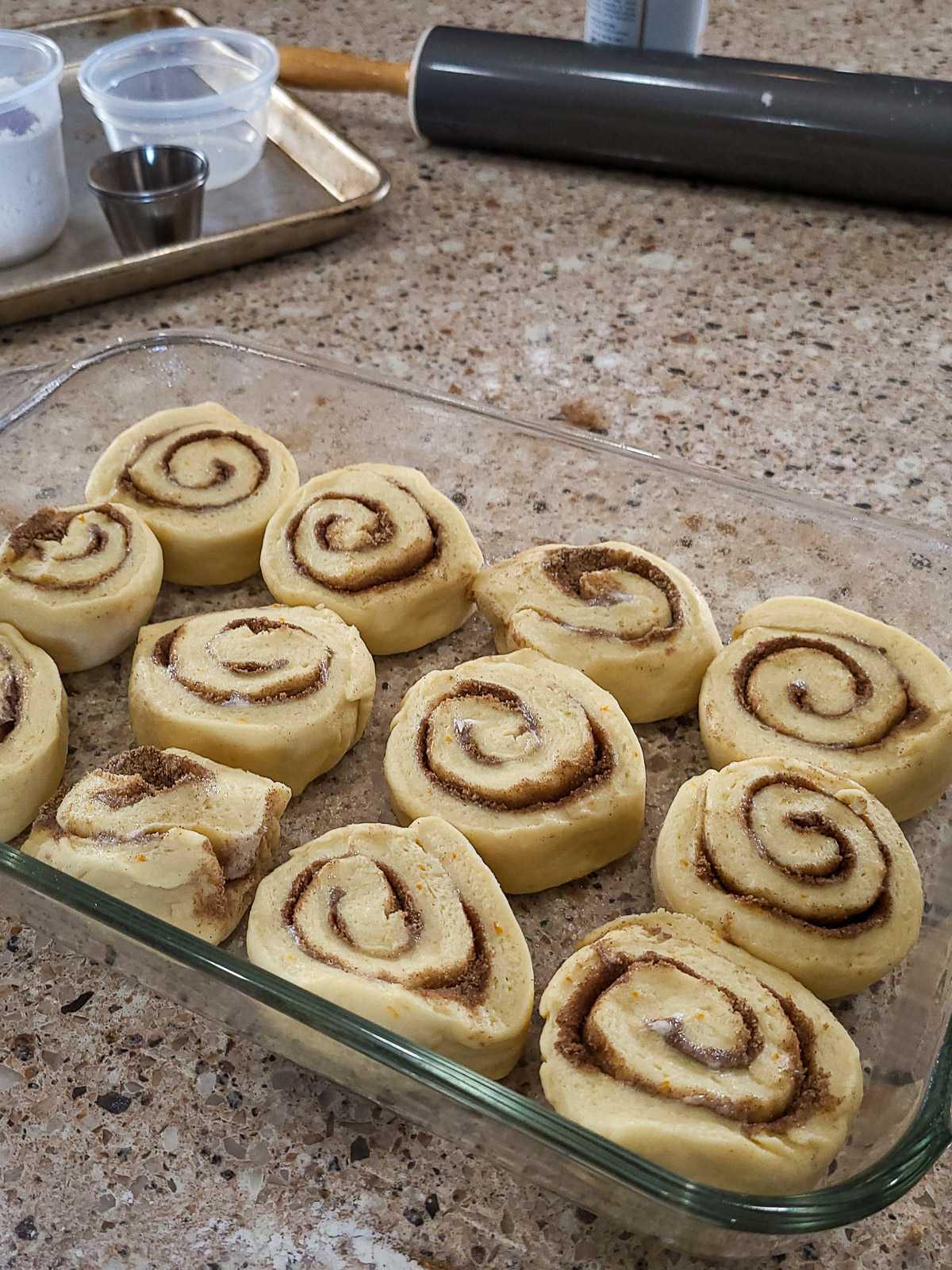 cinnnamon roll dough in a baking dish ready to raise