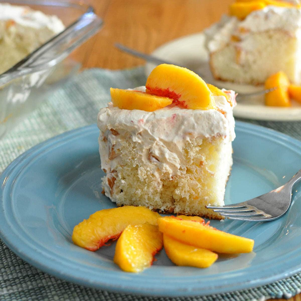a slice of cake with peaches on a blue plate
