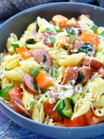 pasta with zucchini, basil, tomatoes and sausage in a gray bowl