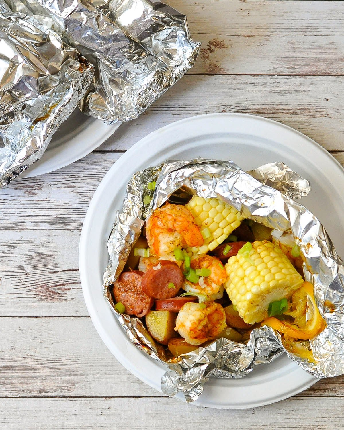 shrimp, sausage, corn, potatoes in foil ready to serve on a paper plate