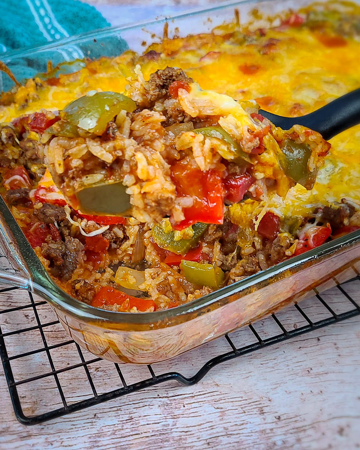 bell pepper casserole being served from a casserole dish with a black spoon