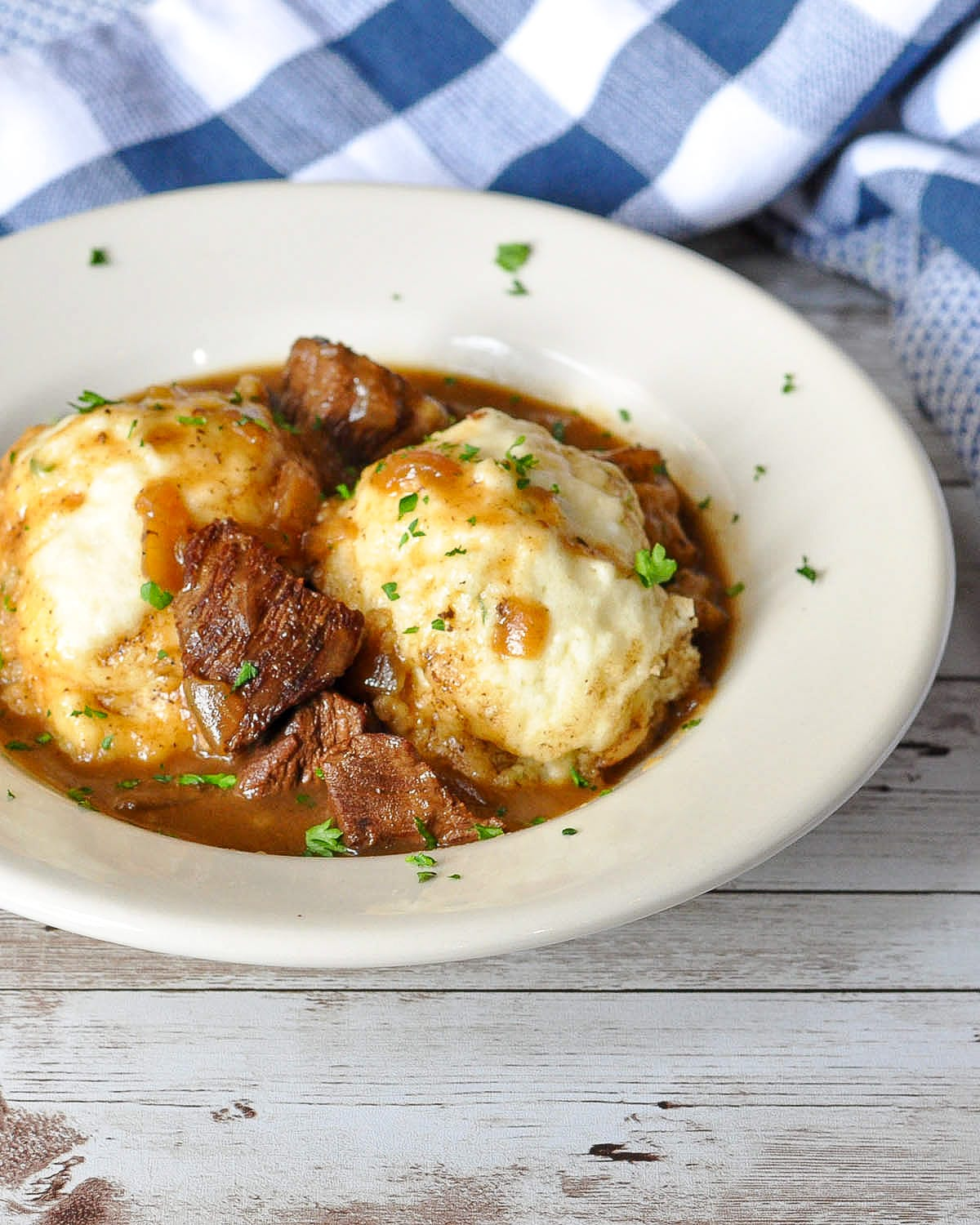 beef and dumplings in a white bowl with blue towels in the background