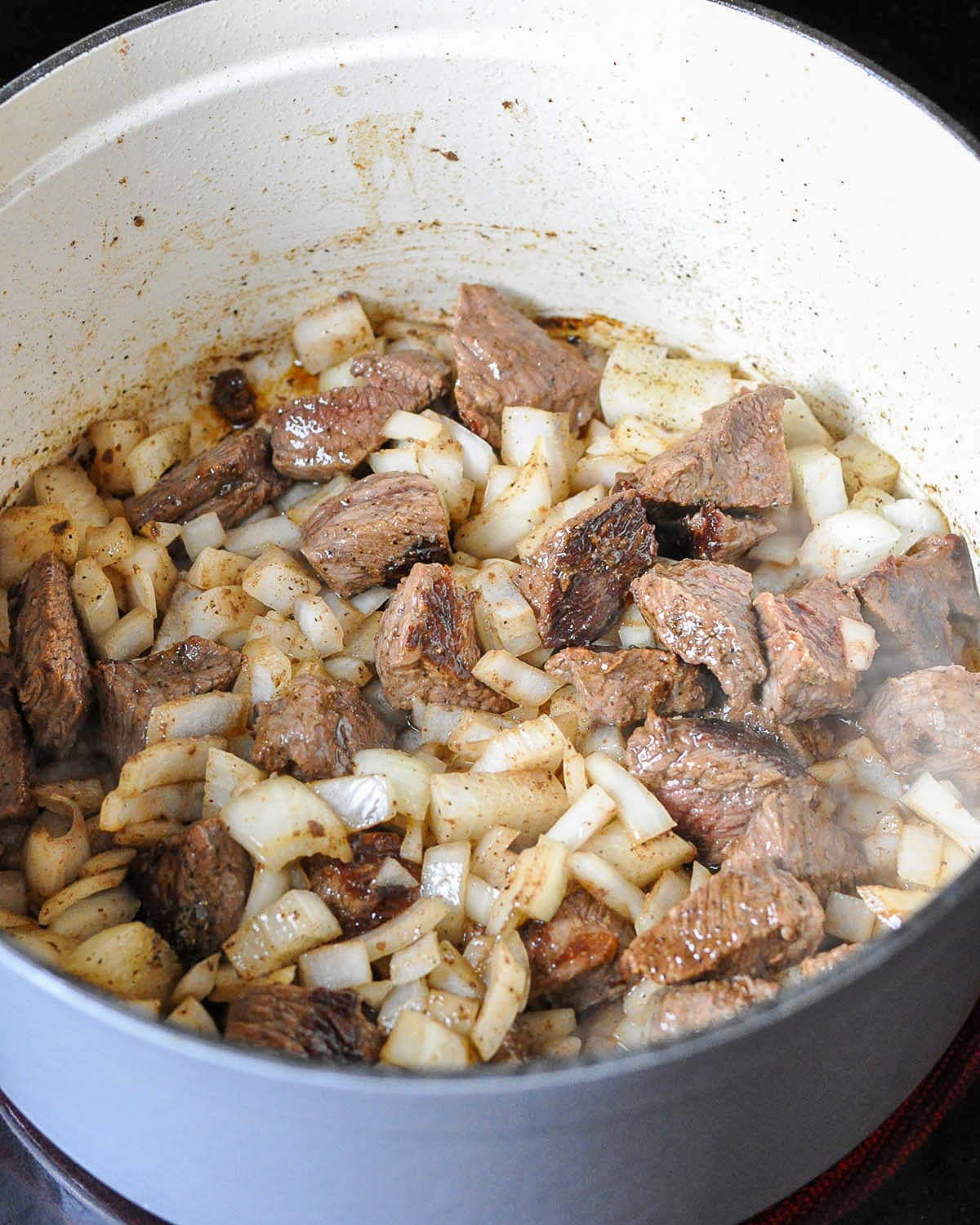 stew meat and onion cooking in a dutch oven