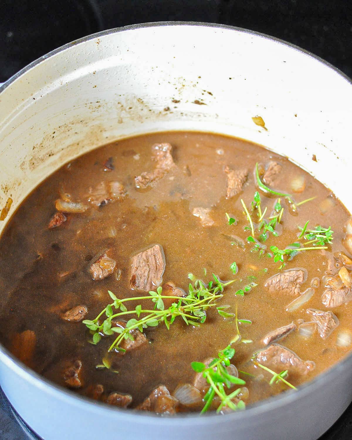 beef stew meat and broth with fresh herbs cooking in a dutch oven