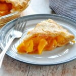 a slice of peach pie on a white and blue plate