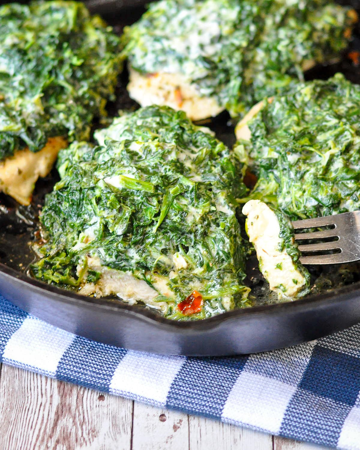 spinach and cheese covered chicken breast in a cast iron skillet