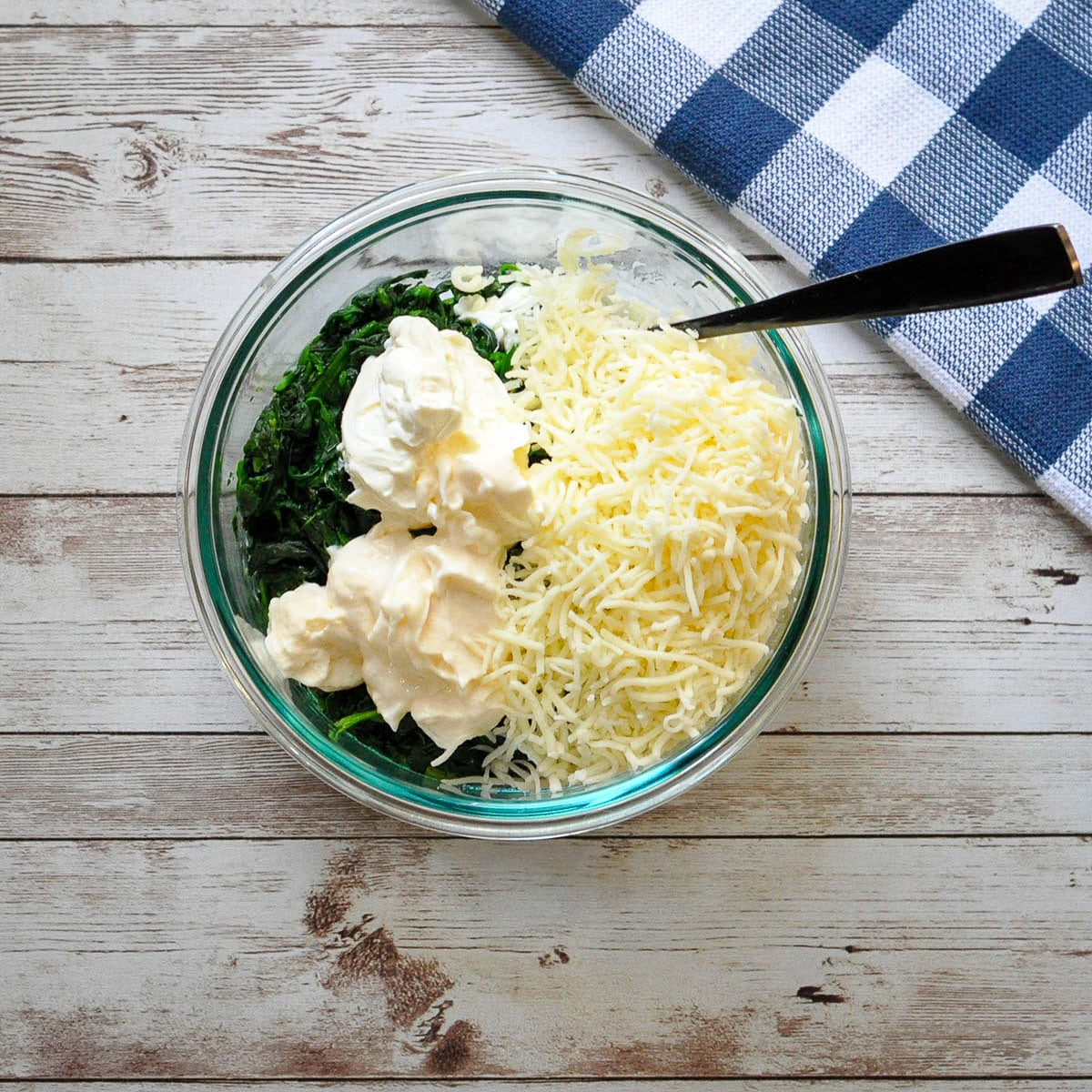 cream cheese, shredded cheese, mayo, and spinach in a bowl