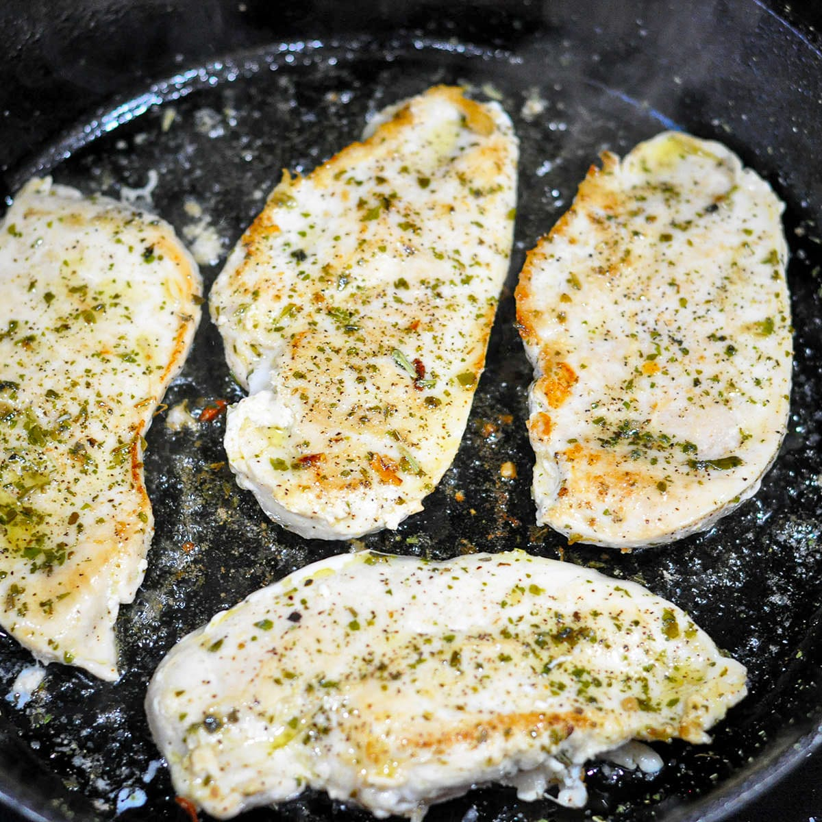 seasoned chicken breast cooking in a cast iron skillet