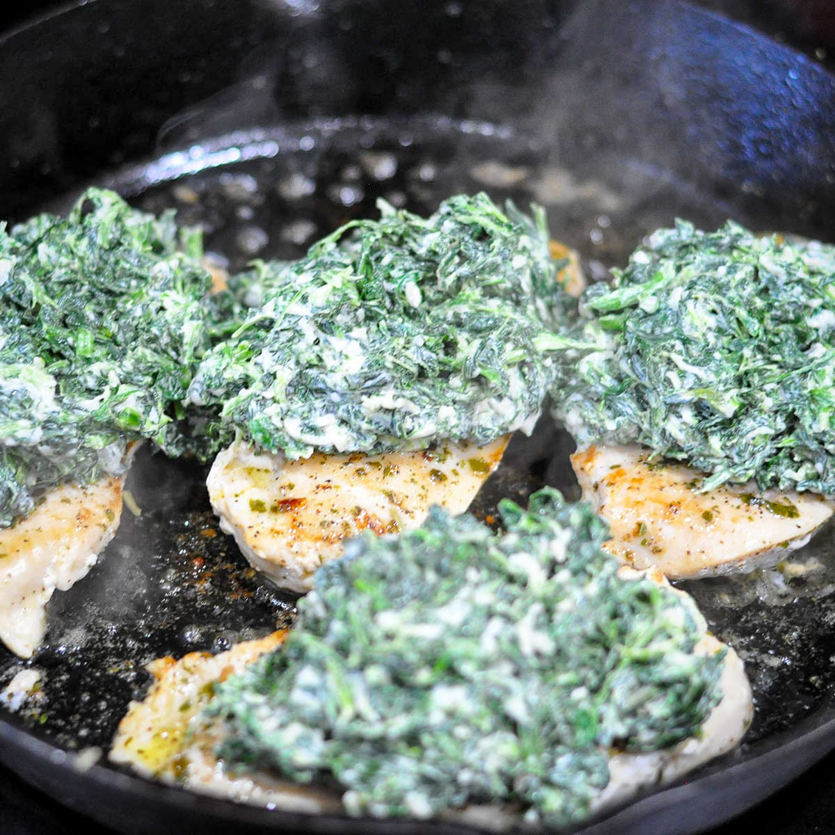 chicken breast cooking in a cast iron skillet topped with spinach and cheese