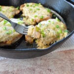 pork chops covered with cheese in a cast iron skillet