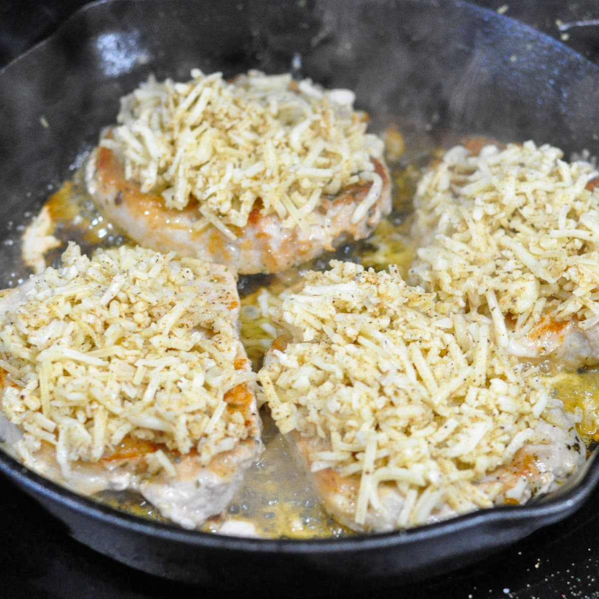 pork chops topped with cheese cooking in a cast iron skillet