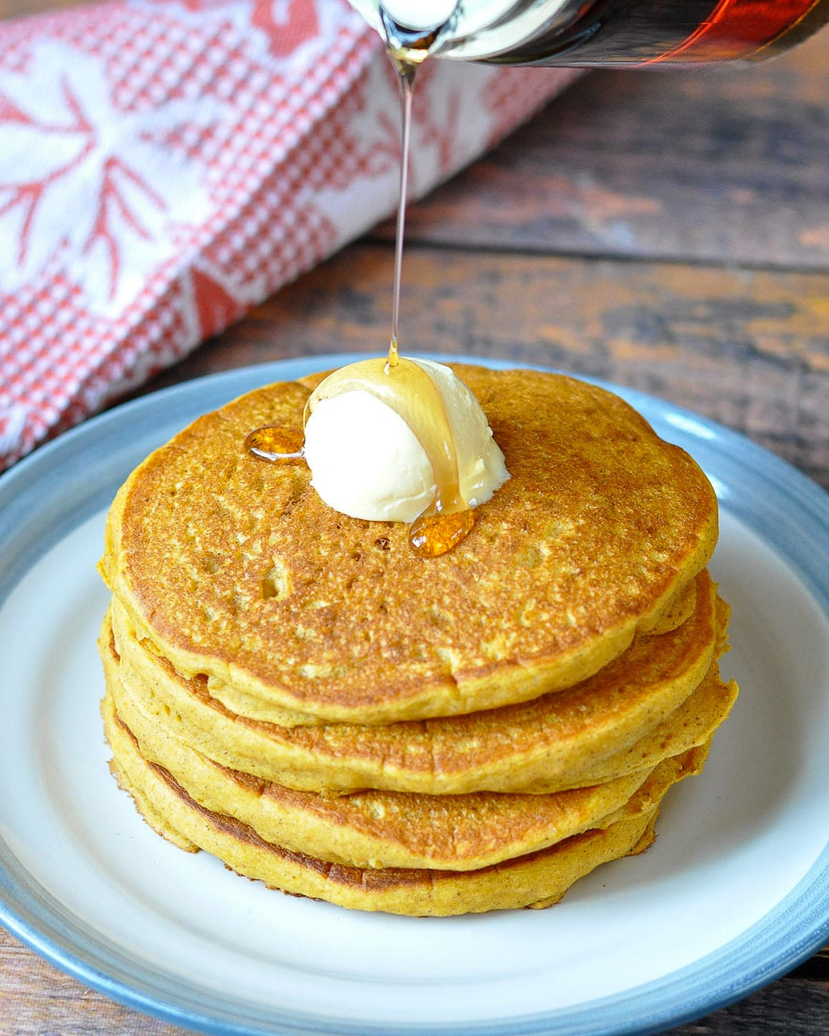 a stack of pumpkin pancakes topped with butter and syrup being poured over the top.