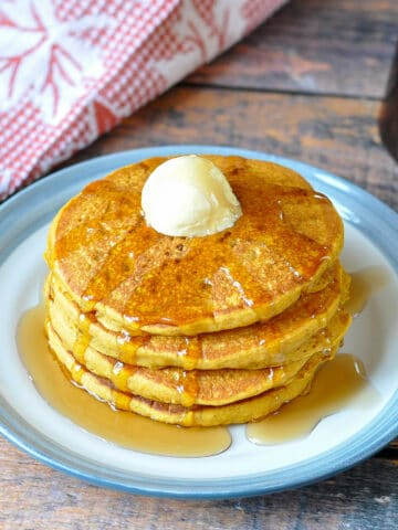 a stack of pumpkin spice pancakes with butter and syrup with a fall themed towel in the back ground