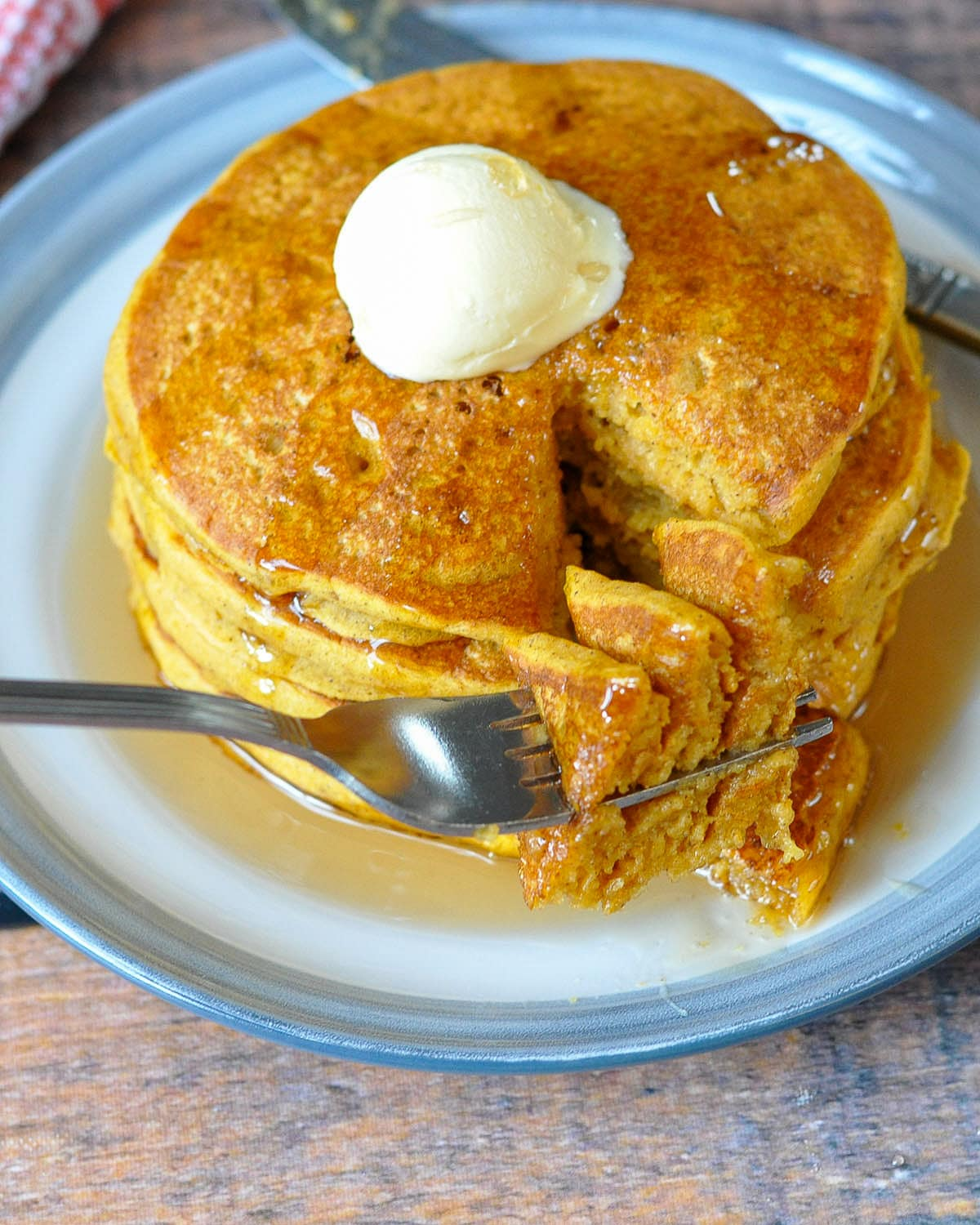 a bite of pumpkin pancakes on a fork next to a stack of pancakes