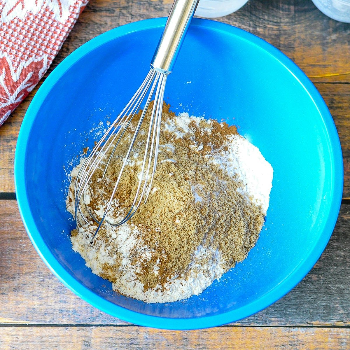 dry ingredients for pumpkin pancakes in a blue bowl with a whisk
